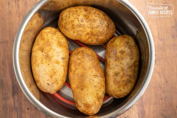 Four russet potatoes in a pot