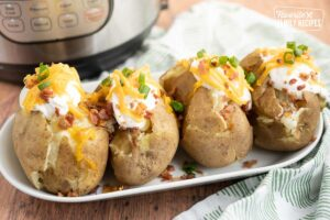 Four baked potatoes, cut in half and loaded with sour cream, cheese, bacon, and green onions