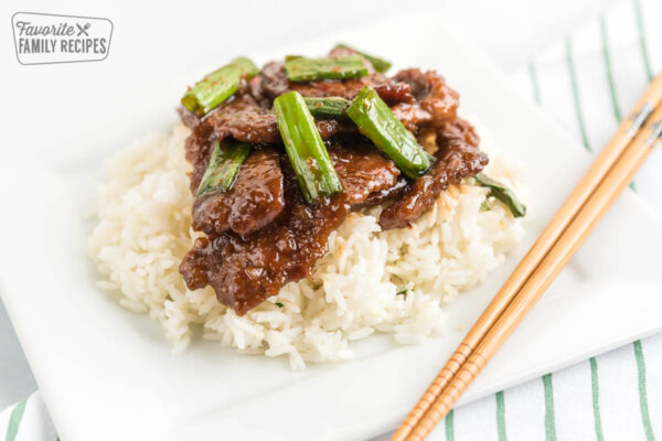 Mongolian Beef topped with green onions on a bed of rice with chopsticks next to the plate.