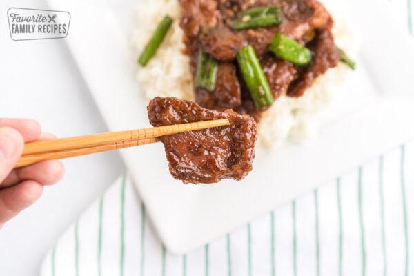 Chopsticks holding up a piece of Mongolian beef