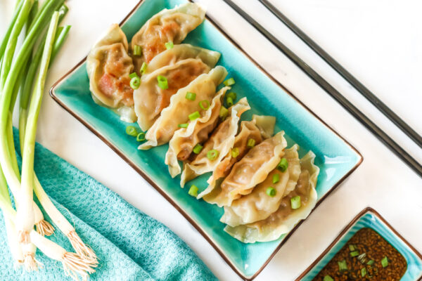 A rectangular plate full of potstickers sitting next to a dipping cup of potsticker sauce, chopsticks, and green onion.