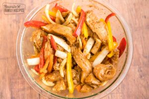Chicken, pepper, and onion slices in a large bowl