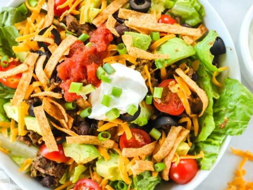 A taco salad made with ground beef, avocado, cheese, tomatoes, chips, salsa, and sour cream. The bowl is next to a halved avocado, cherry tomatoes, and a bowl of salsa.