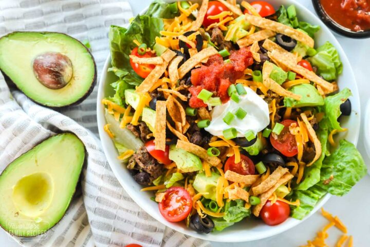 A taco salad made with ground beef, avocado, cheese, tomatoes, chips, salsa, and sour cream. The bowl is next to a halved avocado and a bowl of salsa.