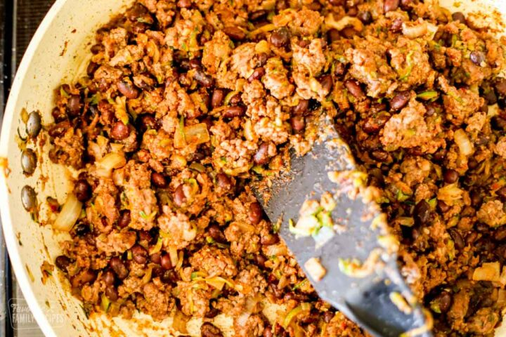 A skillet with browned taco meat to make taco salad.