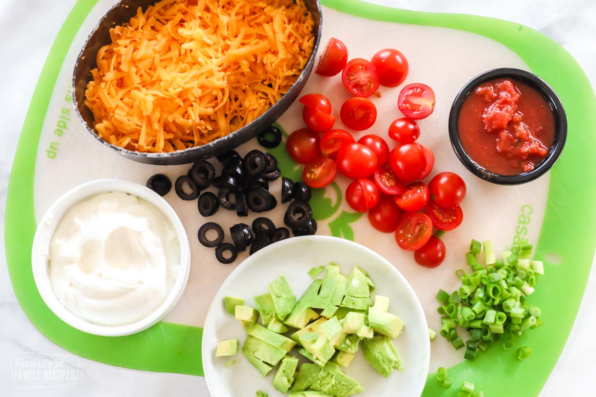 A container of shredded cheese, a cup of sour cream, a cup of salsa, diced avocado, sliced olives, green onion, and cherry tomatoes on a cutting board.