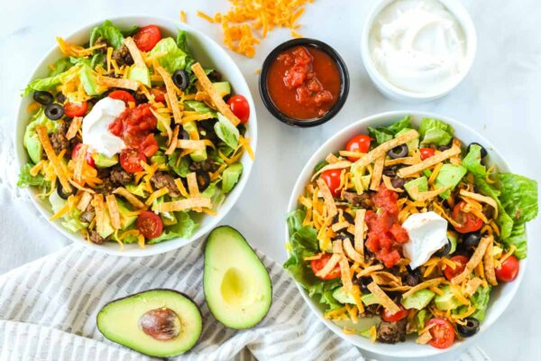 Two bowls of taco salad. An avocado, a cup of sour cream, and a cup of salsa are sitting next to the bowls.