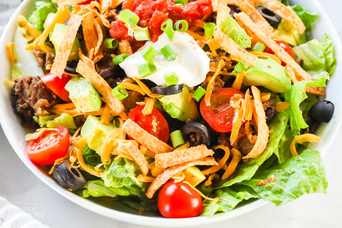 A close up view of a taco salad bowl with ground beef and taco toppings.