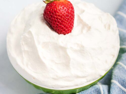 A strawberry on top of a bowl of whipped cream