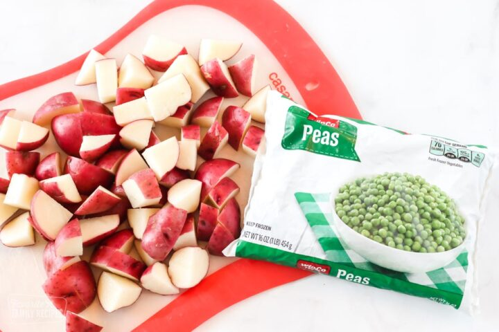 Diced red potatoes on a cutting board next to a package of frozen peas
