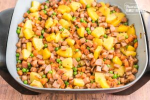 Ham, pineapple, peas, carrots, onions, and garlic in a pan