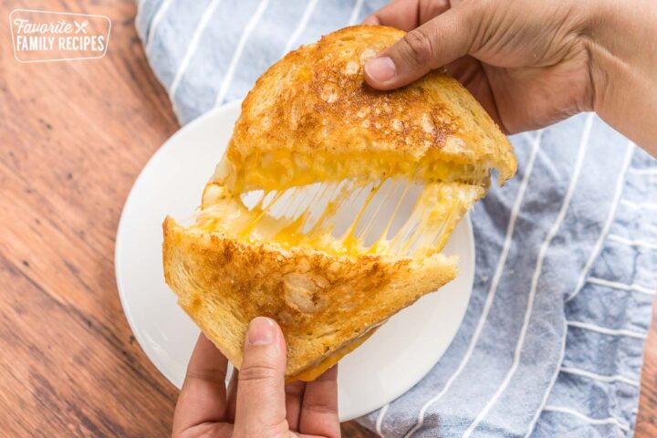 A grilled cheese sandwich being pulled apart