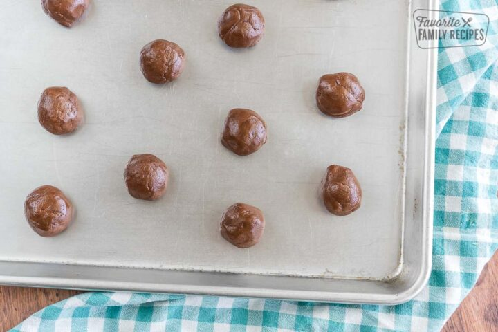 Cookie batter rolled into balls on a baking sheet