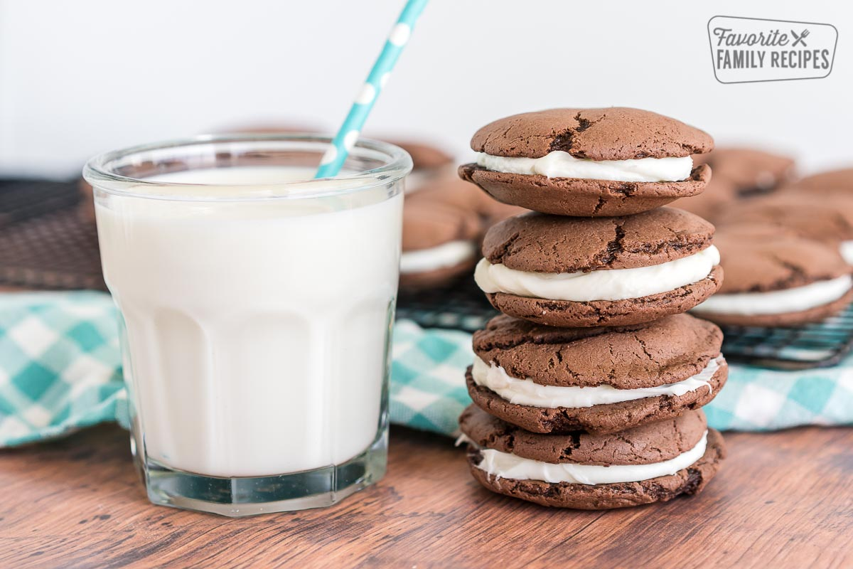A stack of homemade oreos with a glass of milk