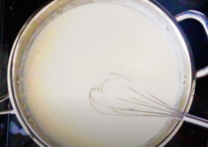 A creamy sauce being made in a skillet with a whisk