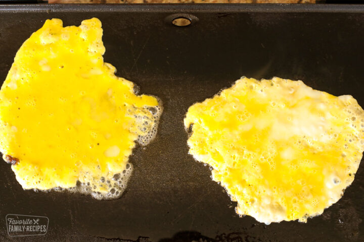 Scrambled eggs on a griddle.