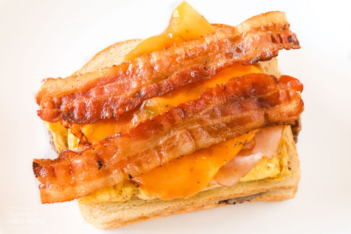 An open faced sandwich showing egg, ham, cheese, and bacon.