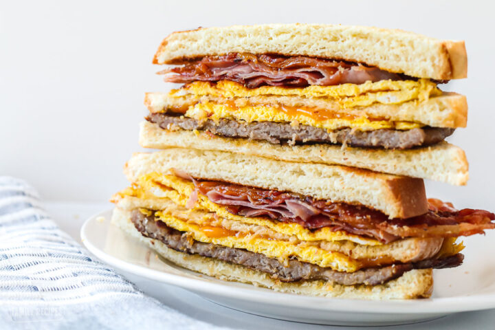 A breakfast sandwich halved with the halves stacked on top of one another.