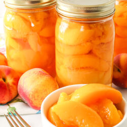 A bowl of sliced peaches in front of bottles of peaches