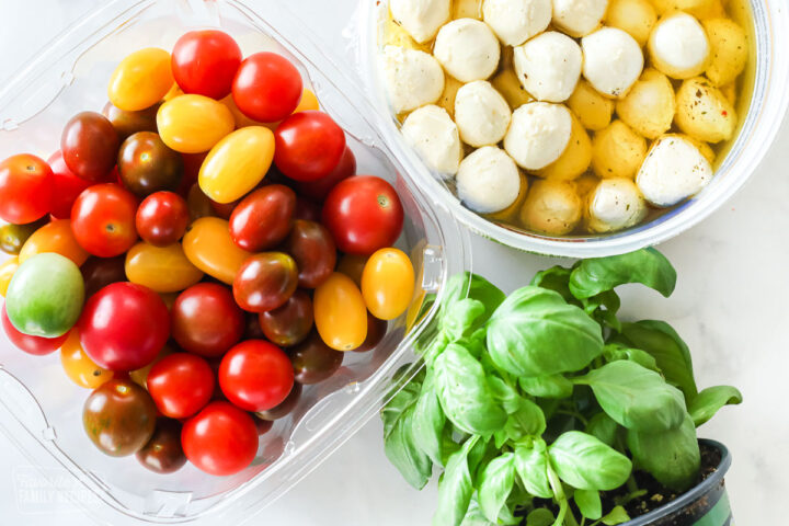A carton of cherry tomatoes, a container of mozzarella balls, and a basil plant.