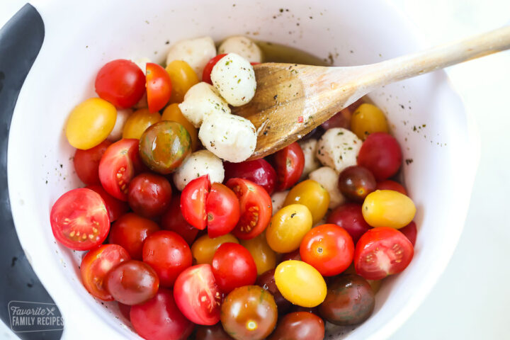 A mixing bowl with cherry tomatoes and mozzarella.