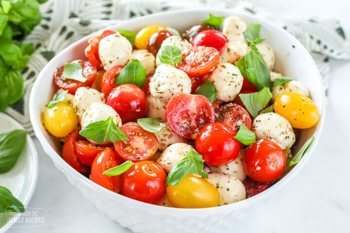 A side-view of a large bowl of caprese salad made with tomatoes, mozzarella, and basil.