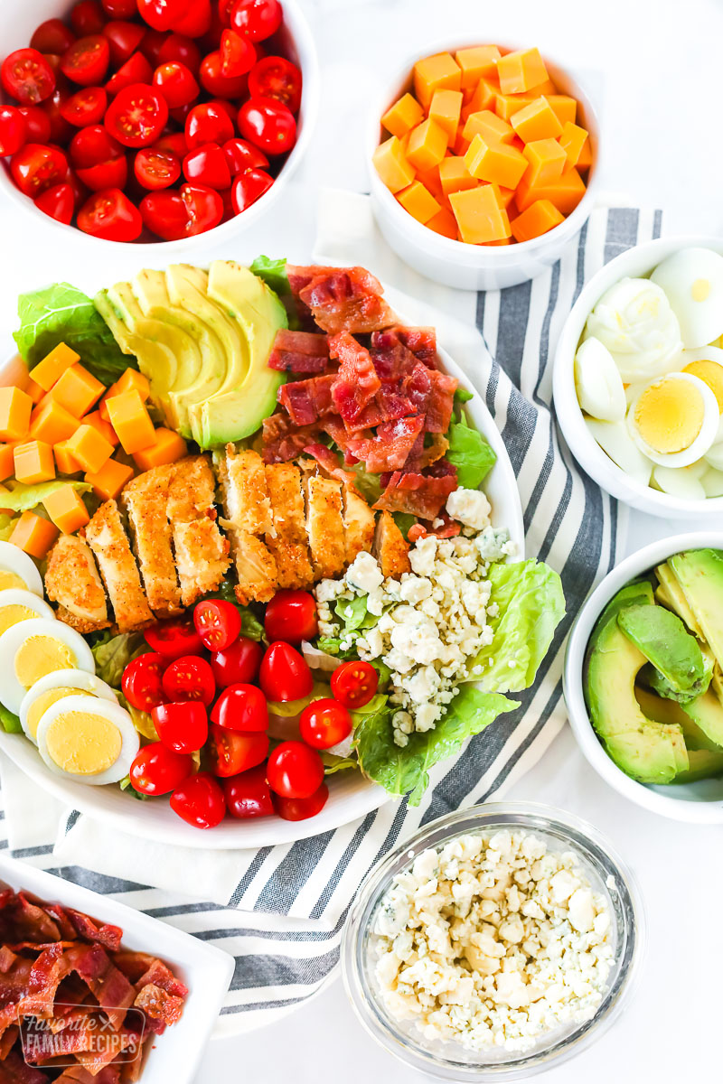 A bowl of Cobb salad with toppings surrounding the bowl including bacon, blue cheese, avocado, egg, cheese, and tomatoes.