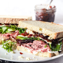 Close up of a roast beef sandwich with bacon jam, blue cheese, and leafy greens on a plate
