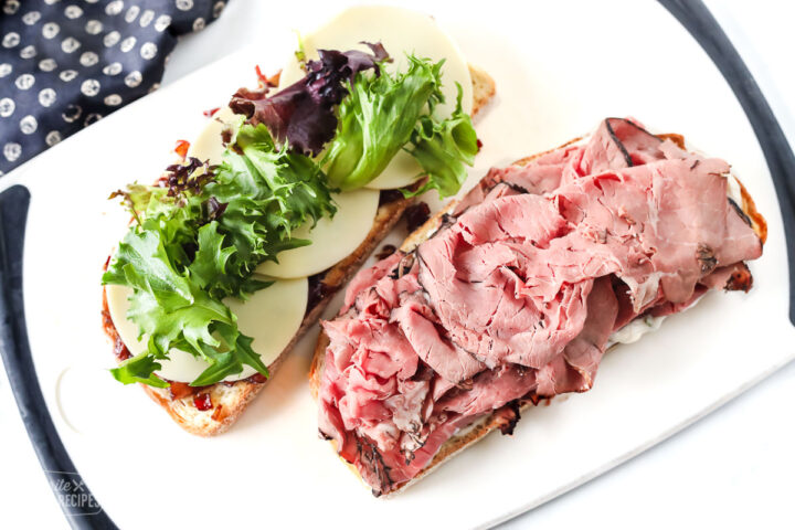 Two slices of artisan bread open-faced. One topped with roast beef and the other with cheese and lettuce.
