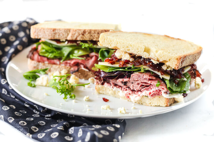 A cold roast beef sandwich on a plate, cut in half to show toppings