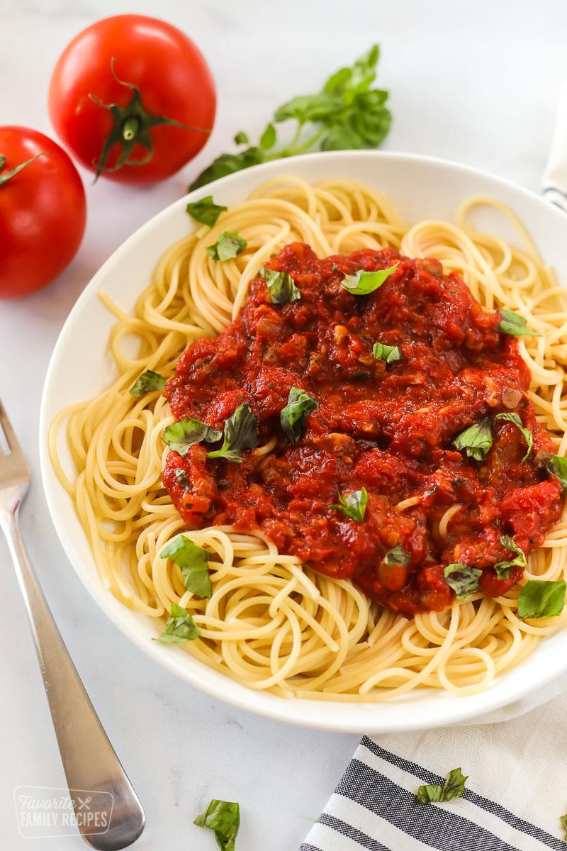 Homemade spaghetti sauce over a bowl of spaghetti noodles