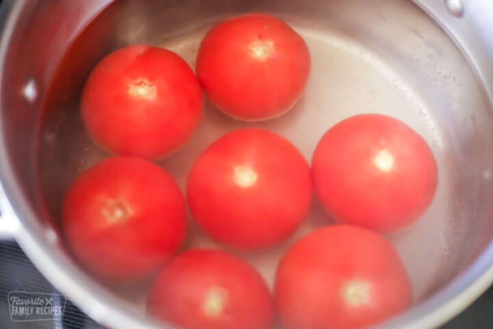 Seven tomatoes in a pot of boiling water