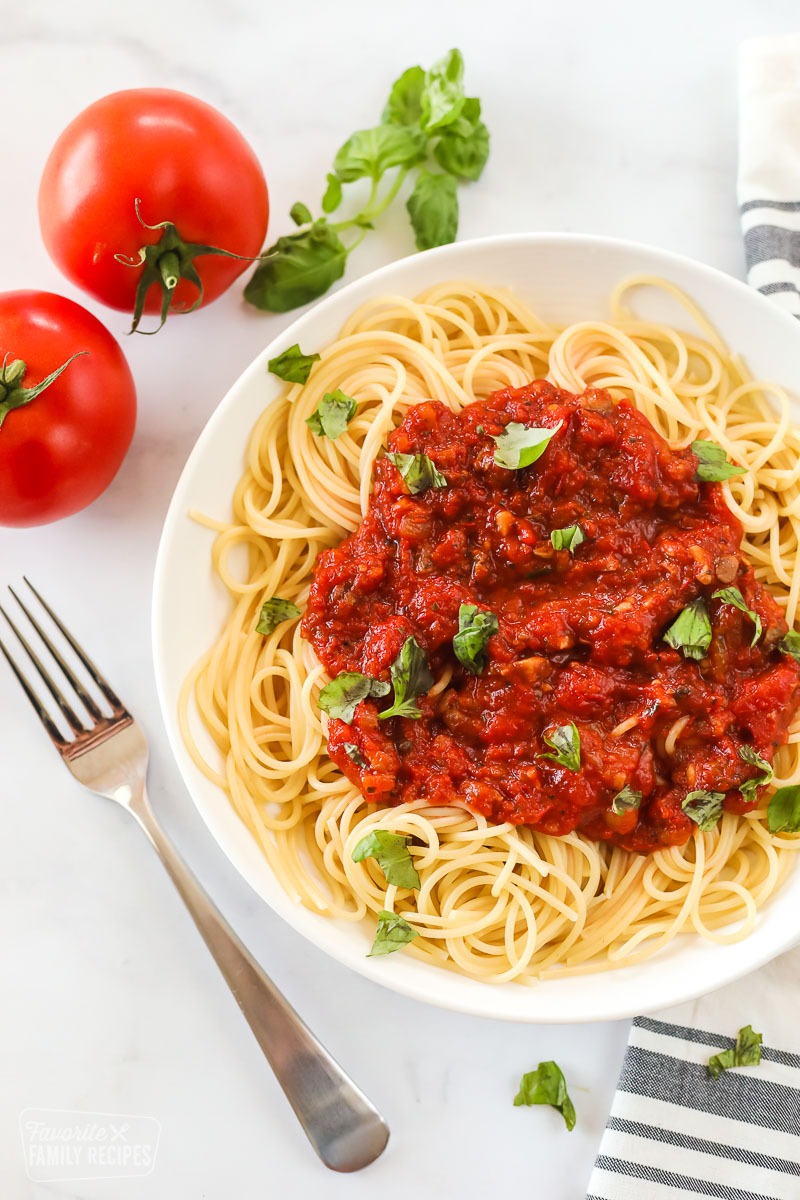 A bowl of spaghetti topped with spaghetti sauce made from scratch