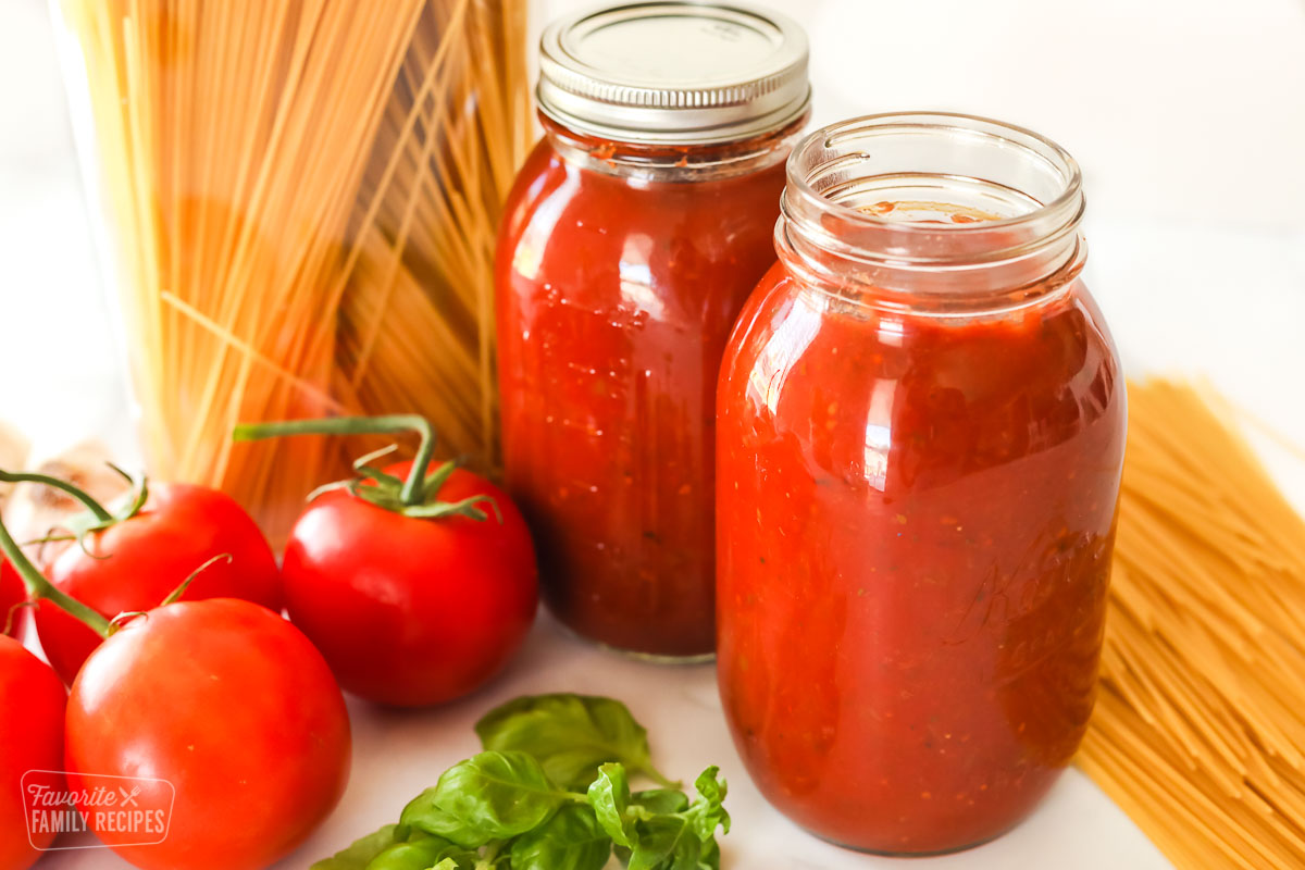 Two jars of homemade canned spaghetti sauce next sauce ingredients