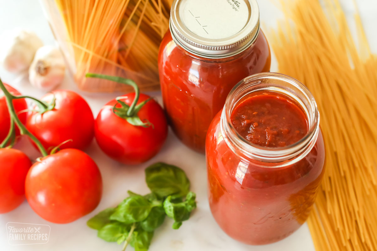 Two glass jars of canned spaghetti sauce next to dry spaghetti