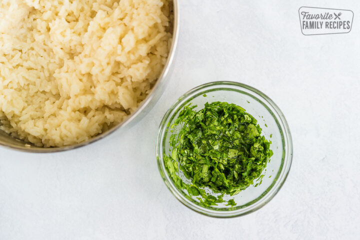 A large pot of cooked white rice and a small bowl of cilantro lime mixture