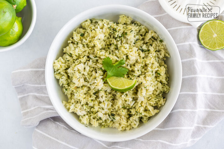 A bowl of cilantro lime rice topped with a lime wedge and a cilantro leaf