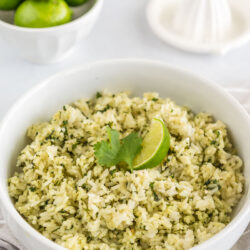 A bowl of cilantro lime rice next to a juicer and a bowl of lime