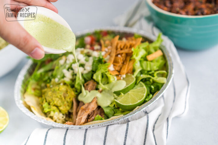 Dressing being poured over a salad