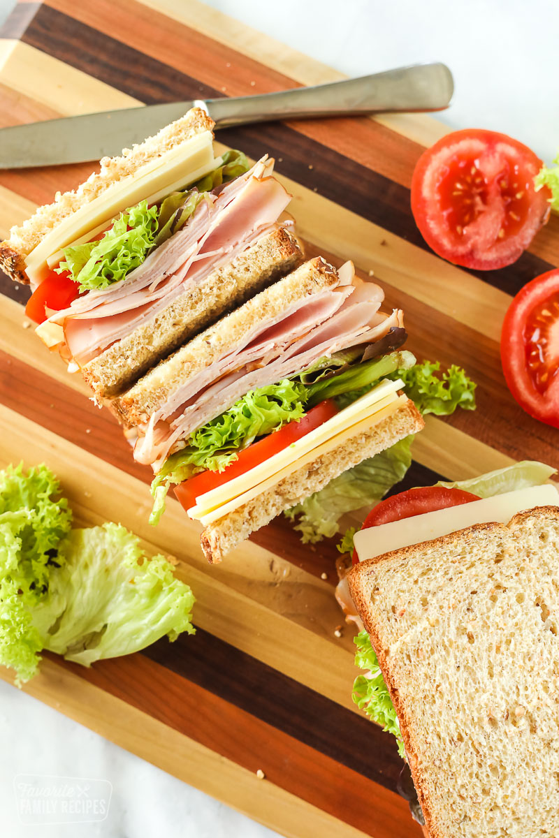 Turkey sandwich on a cutting board cut in half and facing up
