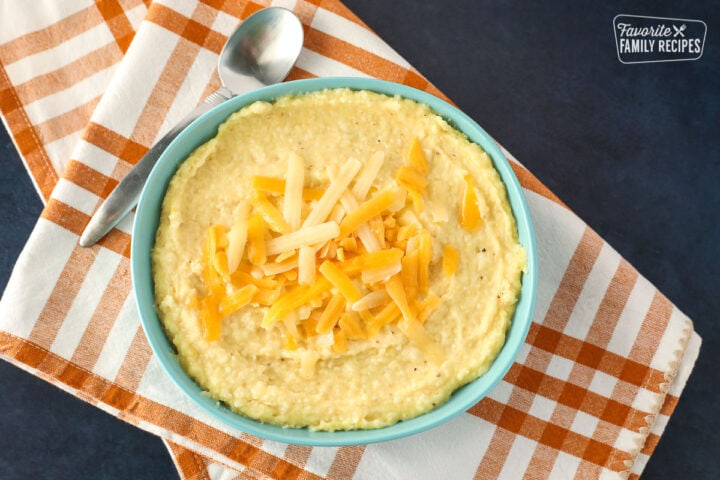 Cheese grits in a bowl with cheese sprinkled on top
