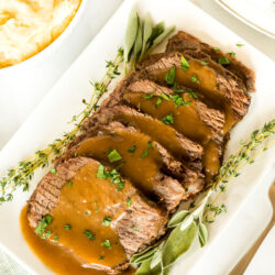 Oven roast beef on a platter with gravy and garnish