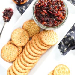 Top view of a jar of bacon jam with crackers