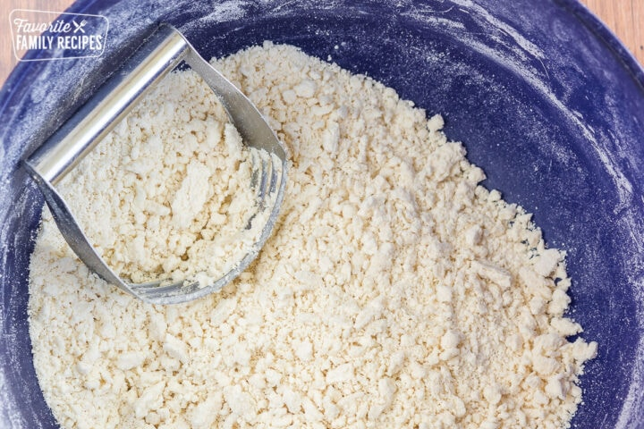 Flour and shortening mixed together in a bowl with a pastry cutter