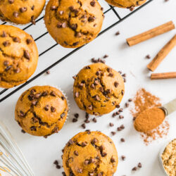 Pumpkin chocolate chip muffins on a cooling rack with some on the counter