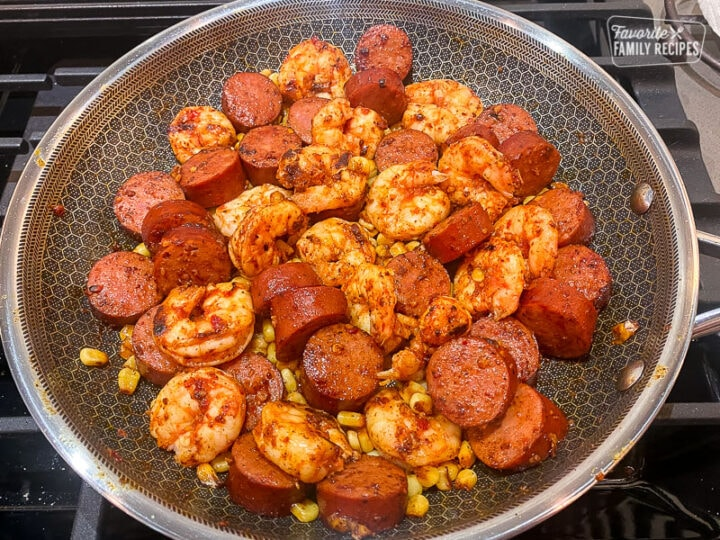 Shrimp, sausage, and corn, cooking in a fry pan