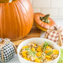 A large pumpkin filled with casserole and a bowl with casserole topped with pumpkin chunks and fresh rosemary