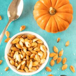 Pumpkin seeds in a bowl next to a tiny pumpkin